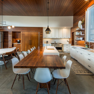 Large contemporary eat-in kitchen designs - Inspiration for a large contemporary l-shaped concrete floor and gray floor eat-in kitchen remodel in Other with an undermount sink, white backsplash, wood backsplash, an island, white countertops, shaker cabinets, white cabinets and stainless steel appliances
