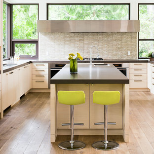 Photo of a large contemporary l-shaped kitchen/diner in Vancouver with flat-panel cabinets, engineered stone countertops, a submerged sink, white cabinets, beige splashback, glass tiled splashback, stainless steel appliances, medium hardwood flooring, an island and brown floors.
