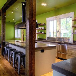 Immagine di una grande cucina a L stile rurale con lavello da incasso, nessun'anta, top in cemento, elettrodomestici in acciaio inossidabile, pavimento in legno massello medio e isola
