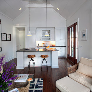Small farmhouse galley open plan kitchen in Atlanta with dark hardwood flooring, shaker cabinets, laminate countertops, white splashback, integrated appliances, white cabinets, a belfast sink and an island.