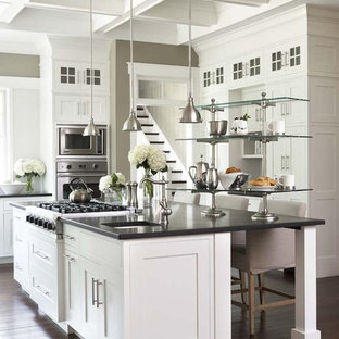 Open concept kitchen - large traditional u-shaped dark wood floor open concept kitchen idea in Charleston with stainless steel appliances, shaker cabinets, white cabinets, an island, granite countertops, an undermount sink and black countertops
