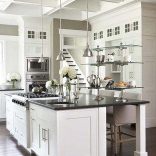 Klassisk inredning av ett stort svart svart kök, med rostfria vitvaror, skåp i shakerstil, vita skåp, mörkt trägolv, en köksö, granitbänkskiva och en undermonterad diskho