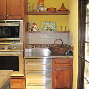 Large tuscan u-shaped ceramic floor enclosed kitchen photo in San Francisco with raised-panel cabinets, dark wood cabinets, stainless steel countertops, multicolored backsplash, ceramic backsplash, stainless steel appliances, a farmhouse sink and an island