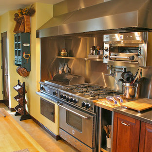 Tuscan u-shaped enclosed kitchen photo in San Francisco with raised-panel cabinets, dark wood cabinets, stainless steel countertops, metallic backsplash and stainless steel appliances