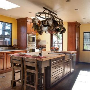 サンフランシスコの大きい地中海スタイルのおしゃれなキッチン (エプロンフロントシンク、レイズドパネル扉のキャビネット、濃色木目調キャビネット、ステンレスカウンター、マルチカラーのキッチンパネル、セラミックタイルのキッチンパネル、シルバーの調理設備の、セラミックタイルの床) の写真