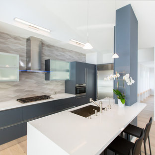 Mid-sized trendy u-shaped light wood floor open concept kitchen photo in San Francisco with an undermount sink, flat-panel cabinets, blue cabinets, gray backsplash, ceramic backsplash, stainless steel appliances, an island and quartz countertops