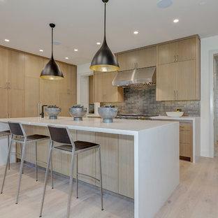 Moderne Küche in L-Form mit flächenbündigen Schrankfronten, hellen Holzschränken, hellem Holzboden, Kücheninsel, Küchenrückwand in Grau, Küchengeräten aus Edelstahl und beigem Boden in San Francisco