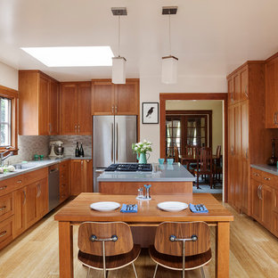 Inspiration for a craftsman u-shaped light wood floor and beige floor eat-in kitchen remodel in San Francisco with shaker cabinets, medium tone wood cabinets, gray backsplash, stainless steel appliances and an island