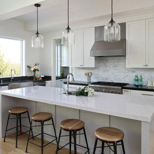 サンフランシスコの大きいカントリー風おしゃれなキッチン (エプロンフロントシンク、シェーカースタイル扉のキャビネット、白いキャビネット、白いキッチンパネル、シルバーの調理設備の、無垢フローリング、茶色い床、黒いキッチンカウンター、ラミネートカウンター、大理石の床) の写真