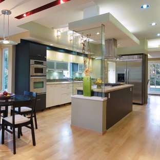 Inspiration for a mid-sized modern l-shaped open plan kitchen in San Francisco with an undermount sink, flat-panel cabinets, yellow cabinets, limestone benchtops, glass tile splashback, stainless steel appliances, medium hardwood floors, with island and brown floor.