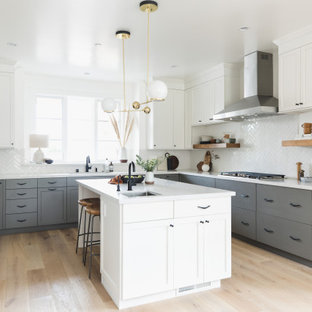 Large classic u-shaped open plan kitchen in San Francisco with a submerged sink, shaker cabinets, grey cabinets, engineered stone countertops, white splashback, ceramic splashback, stainless steel appliances, medium hardwood flooring, an island, brown floors and yellow worktops.