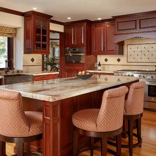 Offene, Große Klassische Küche in L-Form mit Landhausspüle, dunklen Holzschränken, Granit-Arbeitsplatte, Küchenrückwand in Beige, Kalk-Rückwand, Küchengeräten aus Edelstahl, braunem Holzboden, profilierten Schrankfronten, Kücheninsel, braunem Boden und beiger Arbeitsplatte in San Francisco