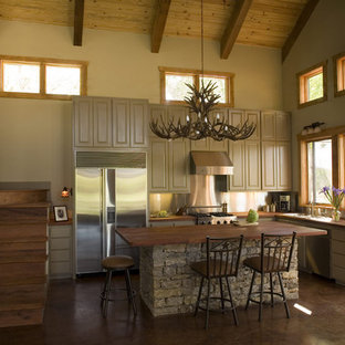 Inspiration for a mid-sized country l-shaped eat-in kitchen in Austin with raised-panel cabinets, beige cabinets, stainless steel appliances, with island, a drop-in sink, wood benchtops, grey splashback, metal splashback and brown floor.
