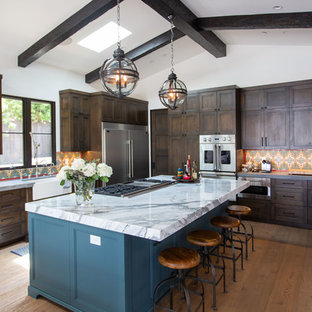 Mediterranean kitchen ideas - Inspiration for a mediterranean u-shaped medium tone wood floor and brown floor kitchen remodel in Los Angeles with a farmhouse sink, recessed-panel cabinets, blue cabinets, multicolored backsplash, stainless steel appliances, an island and white countertops