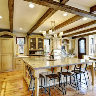 This is an example of a large country u-shaped open plan kitchen in Los Angeles with a farmhouse sink, beaded inset cabinets, distressed cabinets, limestone benchtops, black appliances, light hardwood floors and with island.