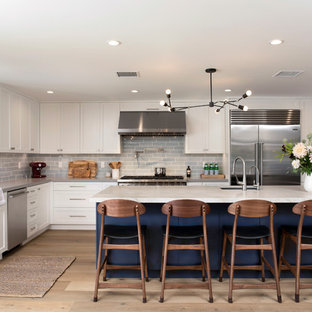 Large transitional kitchen ideas - Example of a large transitional l-shaped light wood floor kitchen design in Los Angeles with shaker cabinets, white cabinets, quartzite countertops, blue backsplash, stainless steel appliances, an island, gray countertops, an undermount sink and subway tile backsplash