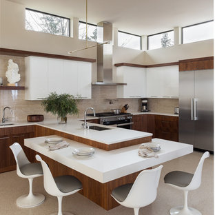 Contemporary eat-in kitchen inspiration - Inspiration for a contemporary u-shaped beige floor eat-in kitchen remodel in Seattle with an undermount sink, flat-panel cabinets, medium tone wood cabinets, beige backsplash, stainless steel appliances, a peninsula and white countertops