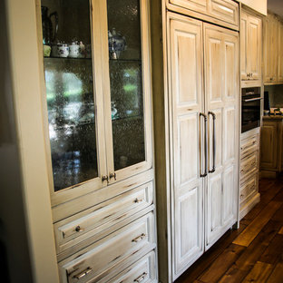 This is an example of a medium sized rustic u-shaped open plan kitchen in Miami with a built-in sink, raised-panel cabinets, distressed cabinets, marble worktops, beige splashback, mosaic tiled splashback, stainless steel appliances, plywood flooring, an island, brown floors and multicoloured worktops.