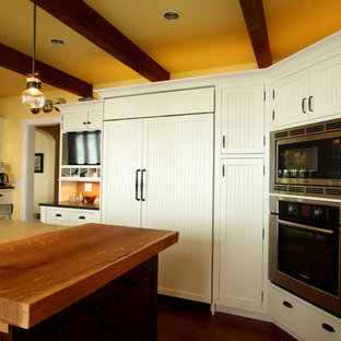 Large farmhouse eat-in kitchen designs - Large farmhouse u-shaped medium tone wood floor eat-in kitchen photo in Other with a triple-bowl sink, beaded inset cabinets, white cabinets, granite countertops, multicolored backsplash, stone tile backsplash, paneled appliances and an island