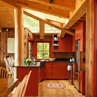 This is an example of a country u-shaped kitchen in Portland Maine with a farmhouse sink, red cabinets, soapstone benchtops, stainless steel appliances, medium hardwood floors and window splashback.