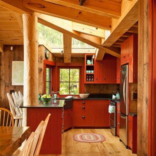 Idéer för ett rustikt u-kök, med en rustik diskho, röda skåp, bänkskiva i täljsten, rostfria vitvaror, mellanmörkt trägolv och fönster som stänkskydd