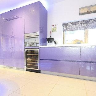 Modern inredning av ett stort kök med öppen planlösning, med en nedsänkt diskho, släta luckor, lila skåp, bänkskiva i koppar, grönt stänkskydd, glaspanel som stänkskydd, svarta vitvaror, klinkergolv i porslin, en köksö och vitt golv