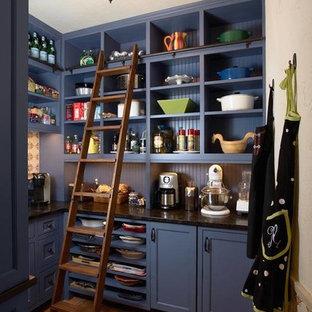 Cette image montre une grand arrière-cuisine rustique en U avec un placard avec porte à panneau encastré, des portes de placard bleues, une crédence bleue, une crédence en bois, un sol en brique et aucun îlot.