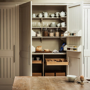 Inspiration for a cottage kitchen pantry remodel in London with beige cabinets
