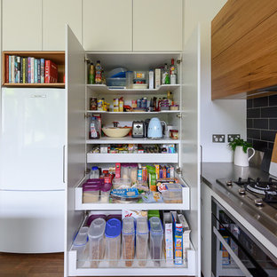 This is an example of a small modern kitchen pantry in Melbourne with flat-panel cabinets, white cabinets, stainless steel worktops, black splashback, ceramic splashback, stainless steel appliances, medium hardwood flooring and brown floors.