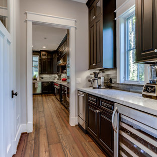 Small craftsman enclosed kitchen photos - Small arts and crafts galley medium tone wood floor enclosed kitchen photo in DC Metro with raised-panel cabinets, dark wood cabinets, marble countertops, gray backsplash, stone tile backsplash, stainless steel appliances and no island