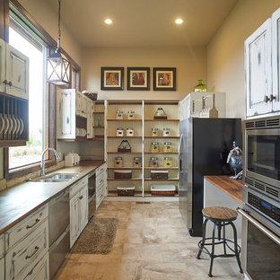 Zweizeilige, Große Landhausstil Küche ohne Insel mit Doppelwaschbecken, profilierten Schrankfronten, Schränken im Used-Look, Arbeitsplatte aus Holz, Küchengeräten aus Edelstahl und Keramikboden in Denver