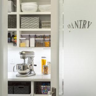 Photo of a large transitional kitchen pantry in Boston with white cabinets, quartzite benchtops, white splashback, ceramic splashback, with island, white benchtop and open cabinets.