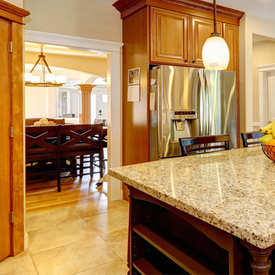 Mid-sized arts and crafts l-shaped kitchen pantry photo in Other with raised-panel cabinets, medium tone wood cabinets, granite countertops, beige backsplash, ceramic backsplash, stainless steel appliances and an island