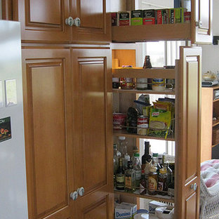 Photo of a medium sized traditional u-shaped kitchen pantry in Other with raised-panel cabinets, light wood cabinets, granite worktops, white appliances, ceramic flooring and no island.