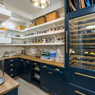 ポートランドのカントリー風おしゃれなキッチン (オープンシェルフ、青いキャビネット、木材カウンター、白いキッチンパネル、淡色無垢フローリング、アイランドなし、ベージュの床、パネルと同色の調理設備) の写真