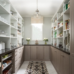 Example of a mid-sized country u-shaped gray floor and porcelain floor kitchen pantry design in Chicago with flat-panel cabinets, medium tone wood cabinets, solid surface countertops and no island
