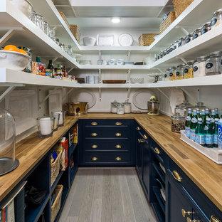 Foto de cocina en U, campestre, con despensa, armarios con paneles empotrados, puertas de armario azules, encimera de madera, suelo de madera clara, suelo gris y encimeras marrones