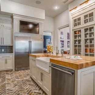 На фото: кухни в классическом стиле с раковиной в стиле кантри, столешницей из кварцита, фартуком из керамогранитной плитки, техникой из нержавеющей стали, кирпичным полом, островом и стеклянными фасадами
