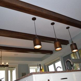 グランドラピッズの大きいトランジショナルスタイルのおしゃれなキッチン (ドロップインシンク、落し込みパネル扉のキャビネット、ヴィンテージ仕上げキャビネット、珪岩カウンター、レンガのキッチンパネル、シルバーの調理設備の、クッションフロア、マルチカラーの床) の写真