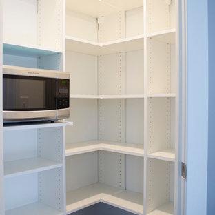 Große Moderne Küche mit Vorratsschrank, offenen Schränken, weißen Schränken, Küchengeräten aus Edelstahl, Teppichboden und braunem Boden in Sonstige