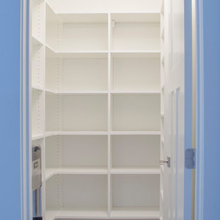 Modern inredning av ett stort skafferi, med öppna hyllor, vita skåp, rostfria vitvaror, heltäckningsmatta och brunt golv