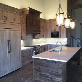 Medium sized rustic galley kitchen/diner in Salt Lake City with shaker cabinets, brown cabinets, composite countertops, beige splashback, ceramic splashback, stainless steel appliances, medium hardwood flooring and an island.