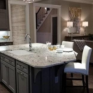 Amerikansk inredning av ett stort kök, med luckor med infälld panel, grå skåp, granitbänkskiva, vitt stänkskydd, rostfria vitvaror, mörkt trägolv och en köksö