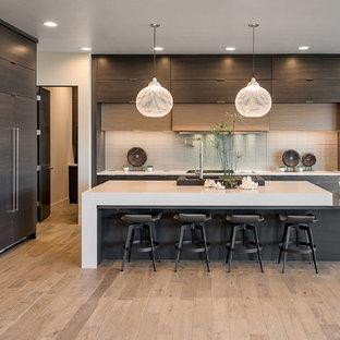 Imagen de cocina lineal, moderna, grande, abierta, con suelo de madera clara, una isla, fregadero bajoencimera, armarios con paneles lisos, puertas de armario de madera en tonos medios, encimera de cuarcita, salpicadero beige, electrodomésticos de acero inoxidable y suelo beige