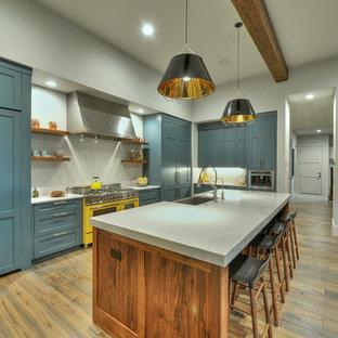 Klassische Küche mit Landhausspüle, Schrankfronten im Shaker-Stil, blauen Schränken, Küchenrückwand in Grau, braunem Holzboden, Kücheninsel und bunten Elektrogeräten in Austin
