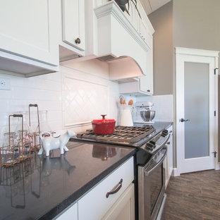 シアトルのラスティックスタイルのおしゃれなキッチン (アンダーカウンターシンク、シェーカースタイル扉のキャビネット、白いキャビネット、御影石カウンター、白いキッチンパネル、サブウェイタイルのキッチンパネル、シルバーの調理設備の、リノリウムの床) の写真