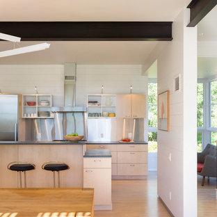 Idee per una cucina scandinava con ante lisce, ante in legno chiaro, paraspruzzi a effetto metallico e elettrodomestici in acciaio inossidabile