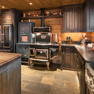 Photo of a large country l-shaped open plan kitchen in Phoenix with a farmhouse sink, raised-panel cabinets, limestone benchtops, timber splashback, black appliances, slate floors, with island, dark wood cabinets and grey floor.