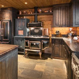 Rustik inredning av ett stort kök, med en rustik diskho, luckor med upphöjd panel, bänkskiva i kalksten, stänkskydd i trä, svarta vitvaror, skiffergolv, en köksö, skåp i mörkt trä och grått golv