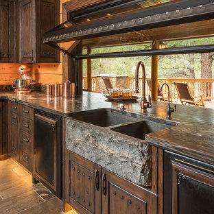Offene, Große Rustikale Küche in L-Form mit Landhausspüle, profilierten Schrankfronten, braunen Schränken, Kalkstein-Arbeitsplatte, Küchenrückwand in Beige, Rückwand aus Holz, schwarzen Elektrogeräten, Schieferboden und Kücheninsel in Phoenix